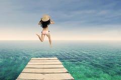 Donna felice che salta al pilastro 1 fotografia stock libera da diritti