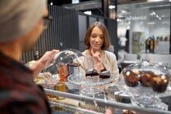 Donna felice che sceglie i dolci al caffè del vegano Immagini Stock Libere da Diritti