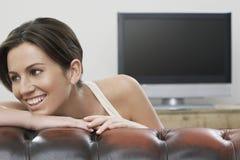 Donna felice che si appoggia Sofa With TV nel fondo immagini stock
