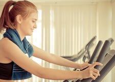Donna felice che si esercita su una macchina della bici di forma fisica Fotografia Stock