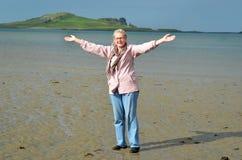 Donna felice che si leva in piedi su una spiaggia Immagine Stock Libera da Diritti
