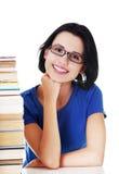 Donna felice che si siede ad uno scrittorio con la pila di libri Fotografia Stock Libera da Diritti
