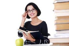 Donna felice che si siede ad uno scrittorio con la pila di libri Immagine Stock Libera da Diritti