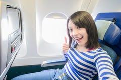 Donna felice che si siede in aeroplano immagini stock libere da diritti