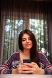 Donna felice che si siede alla tavola Fotografie Stock