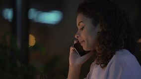 Donna felice che si siede in caffè accogliente e che ha conversazione telefonica, buone notizie video d archivio