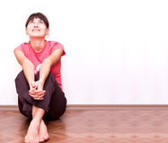Donna felice che si siede dalla parete sul pavimento Fotografie Stock Libere da Diritti