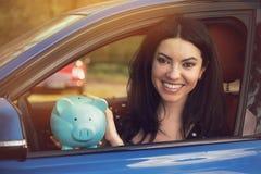Donna felice che si siede dentro la sua automobile con il porcellino salvadanaio Fotografia Stock