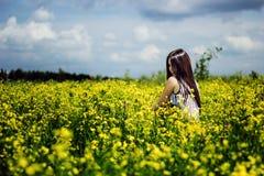 Donna felice che si siede sul giacimento di fiori soleggiato giallo Fotografia Stock Libera da Diritti