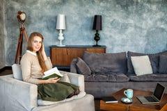 Donna felice che si siede sul sofà e sul libro di lettura Fotografia Stock Libera da Diritti