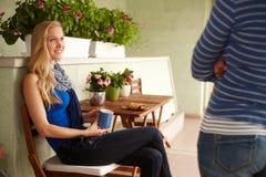 Donna felice che si siede sul terrazzo Immagine Stock