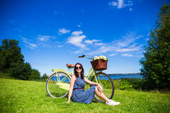 Donna felice che si siede sull'erba con la bicicletta d'annata sul mare Fotografia Stock