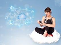 Donna felice che si siede sulla nuvola con la computazione della nuvola Immagine Stock