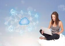 Donna felice che si siede sulla nuvola con la computazione della nuvola Immagine Stock Libera da Diritti
