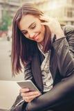Donna felice che si siede sulla via, messaggio di battitura a macchina, chiacchierante su astuto Immagini Stock