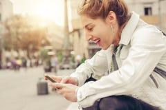 Donna felice che si siede sulla via, messaggio di battitura a macchina, chiacchierante su astuto Fotografie Stock Libere da Diritti