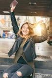Donna felice che si siede sulla via, messaggio di battitura a macchina, chiacchierante su astuto Fotografia Stock