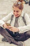 Donna felice che si siede sulla via, messaggio di battitura a macchina, chiacchierante su astuto Fotografia Stock Libera da Diritti