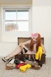 Donna felice che si siede in valigia con calzature che si trovano sul pavimento Fotografia Stock