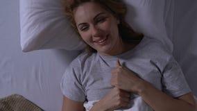 Donna felice che si trova a letto, esaminando test di gravidanza con il risultato positivo stock footage