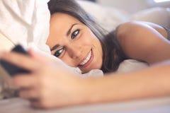 Donna felice che si trova sul letto che legge un messaggio di testo Immagine Stock
