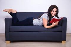 Donna felice che si trova sul sofà e sul libro di lettura a casa Fotografia Stock Libera da Diritti