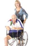 Donna felice che spinge l'uomo di handicap Fotografie Stock