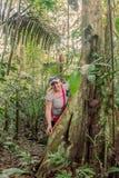 Donna felice che sta accanto ad un albero di capoc fotografia stock