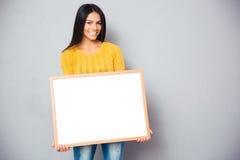 Donna felice che tiene bordo in bianco Fotografia Stock Libera da Diritti