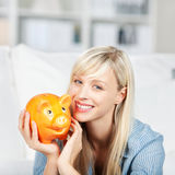 Donna felice che tiene il suo porcellino salvadanaio Fotografia Stock Libera da Diritti