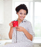Donna felice che tiene una tazza di caffè nella sua cucina Immagine Stock