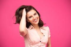 Donna felice che tocca i suoi capelli e che esamina macchina fotografica Fotografie Stock