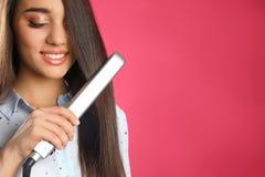 Donna felice che usando il ferro dei capelli sul fondo di colore immagini stock