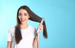 Donna felice che usando il ferro dei capelli sul fondo di colore immagini stock libere da diritti