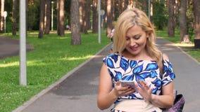 Donna felice che utilizza telefono cellulare mentre camminando nel parco di estate video d archivio
