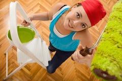 Donna felice che vernicia il soffitto su una scaletta fotografia stock