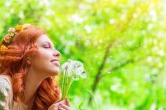 Donna felice con i fiori del dente di leone Fotografia Stock Libera da Diritti