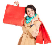 Donna felice con i sacchetti della spesa in cappotto beige di autunno Fotografia Stock