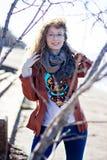 Donna felice con i vetri ed i capelli ricci su fondo soleggiato luminoso Fotografia Stock Libera da Diritti