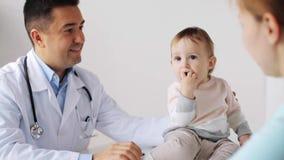 Donna felice con il bambino e medico alla clinica stock footage