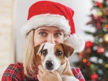 Donna felice con il cane nella decorazione di natale fotografie stock