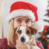 Donna felice con il cane nella decorazione di natale fotografia stock