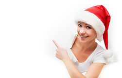 Donna felice con il cappello di natale che dà una occhiata attraverso un foro lacerato in w Fotografia Stock
