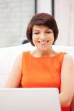 Donna felice con il computer portatile Fotografia Stock