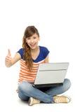 Donna felice con il computer portatile che mostra i pollici in su Fotografie Stock Libere da Diritti