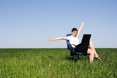 Donna felice con il computer portatile che si siede al campo verde Immagini Stock