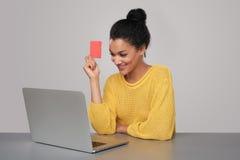 Donna felice con il computer portatile che tiene la carta di credito in banca Immagine Stock