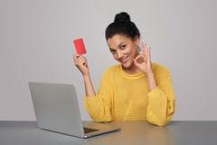 Donna felice con il computer portatile che tiene la carta di credito in banca Fotografia Stock