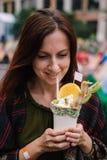 Donna felice con il dessert saporito del frappé Immagine Stock