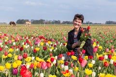 Donna felice con il mazzo di tulipani in un campo variopinto del tulipano Immagini Stock